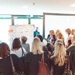 Teilnehmende des HRcamps 2019 stehen zusammen und hören zu