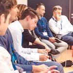 Teilnehmer des HRcamps 2021 sitzen im Stuhlkreis, ein Teilnehmer schreibt etwas auf