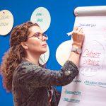 Teilnehmerin schreibt es auf Flipchart bei dem HRcamp 2019