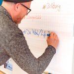 Teilnehmer des HRcamps 2019 schreibt etwas auf das Flipchart