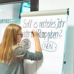 Teilnehmerin des HRcamps in Koblenz schreibt etwas auf die Flipchart