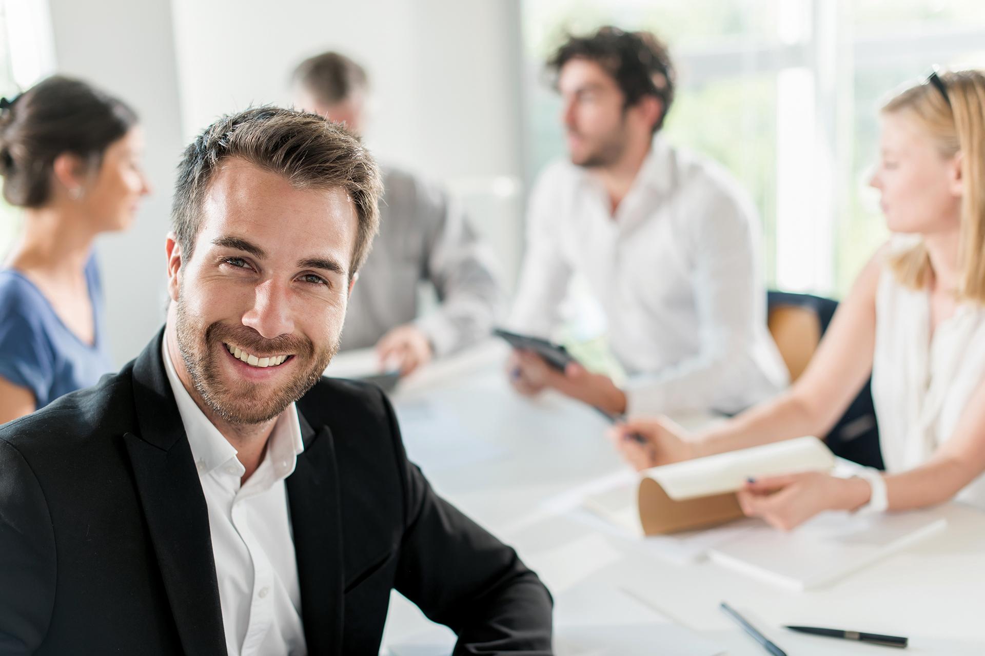 Geprüfter Betriebswirt lächelt in die Kamera während Arbeitskollegen im Hintergrund diskutieren